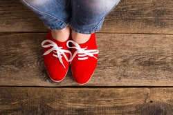 red Sneakers shoes walking on Dirty wooden top view , Canvas shoes walking on wooden