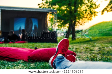 Red snickers shoes on ground and big movie screen in open cinema in green public park.Enjoying and relaxing on summer weekend. - Shutterstock ID 1114506287
