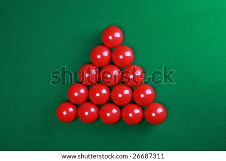 Red snooker balls in triangle on green table