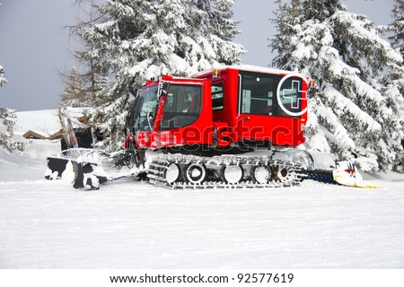 Red snow groomer in the Austrian Alps
