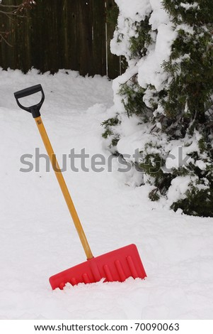Red snow shovel standing up in deep snow.