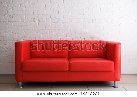 Red sofa and white brick wall - stock photo