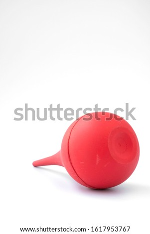 Red soft bulb Enema Syringe or Ear Ulcer Syringe isolated on white background. Red bulb enema syringe is medical equipment used to clean lower colon by spraying water via anal. Douche Cleaner concept.