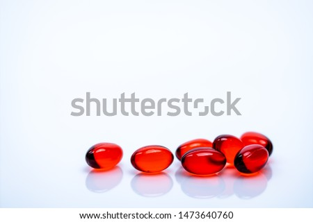 Red soft gel capsule pills isolated on white background. Pile of red soft gelatin capsule. Vitamins and dietary supplements concept. Pharmaceutical industry. Pharmacy drug store. Health care products.