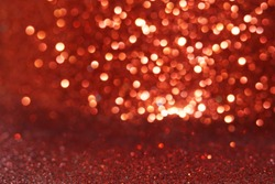 Red Sparkling Lights Festive background with texture. Abstract Christmas twinkled bright bokeh defocused and Falling stars. Winter Card or invitation