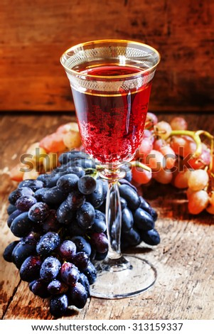 Red sparkling wine in the glass, blue and pink grapes in the wine cellar, selective focus