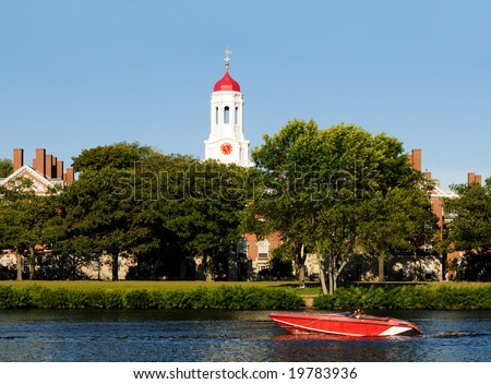 Red speed boat on Charles River passing by Harvard University Dunster House.