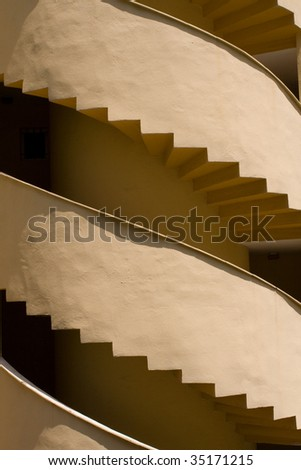 Red spiral stairs in spain, visible two parts, sunny day, detail. - stock photo