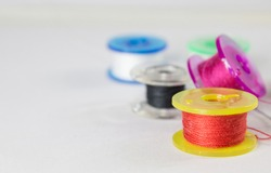 Red spool with others colorful spools on a white background