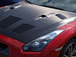 Red sportcars with carbon fiber hood.