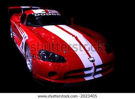 Red sports car on a black background. Editorial use.