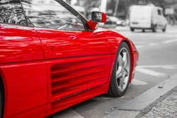 Red sports car on city streets, black and white background
