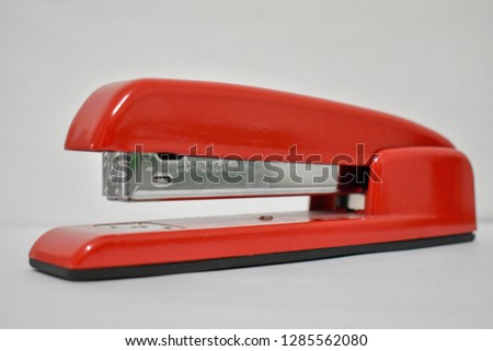 red stapler close up white background office supplies