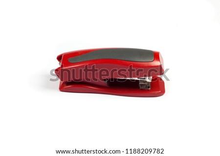 Red stapler on white background.