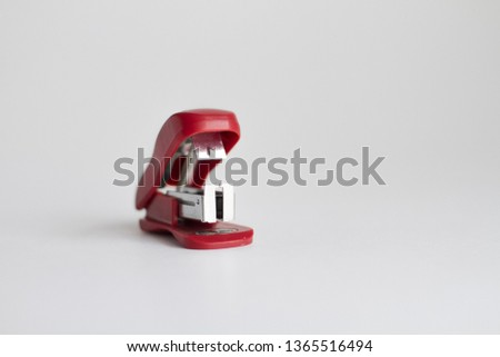 Red stationery stapler on a white background