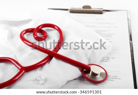 Red stethoscope, medical record and uniform on white background