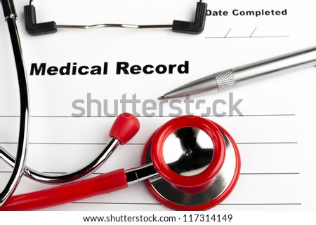 Red stethoscope on  blue clipboard  with medical record close-up with silver colored pen