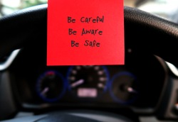 Red sticky note with text written BE CAREFUL BE AWARE BE SAFE , on the car steering wheel , to remind driver to drive carefully