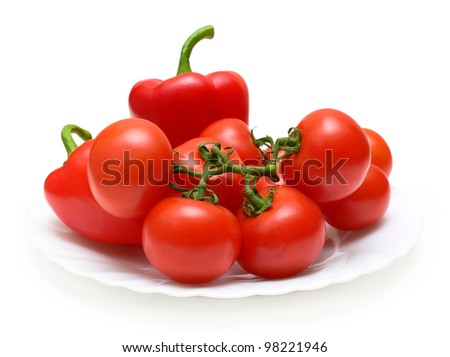 Red still life with vegetables on plate: bell peppers and tomatoes.