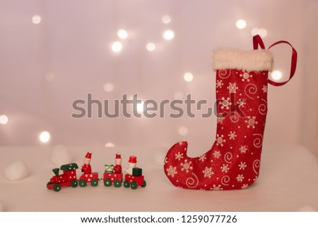 red stocking with deer for handmade gifts stands against the background of Christmas lights, candles and balls #1259077726