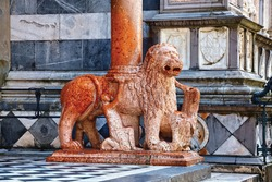 Red stone lion sculpture of the Cappella Colleoni (was built with marble elements between 1472 and 1476) of the Basilica di Santa Maria Maggiore (Saint Mary church). Bergamo, Italy.