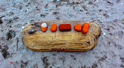 Red stones placed on driftwood in sand at the lake