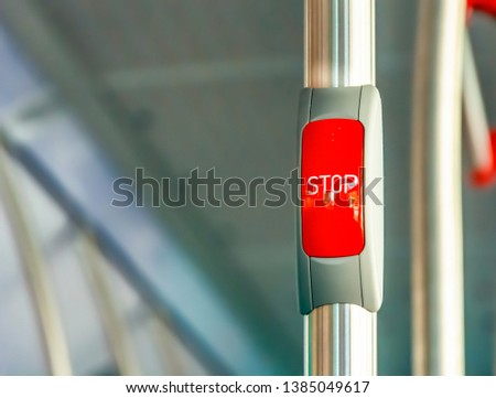 Red stop button on the metal handrail of a bus. Public transport. Public transportation