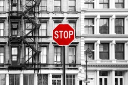 Red stop sign against background of old black and white buildings in the SoHo neighborhood of Manhattan, New York City NYC