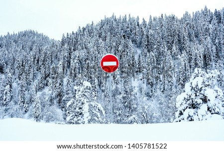 Red stop sign in winter in snowy conditions, in snowy mountains  #1405781522
