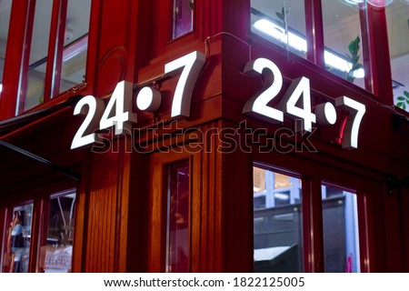 Photo of  red store on the corner with a luminous sign 24/7, English style red store with glass windows, a night scene of building facade lighting details.