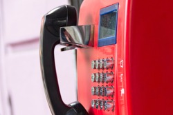 Red street payphone with round stainless steel buttons close-up. An outdated way of communication.