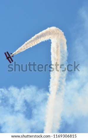 Red stunt biplane flying on cloudy blue sky performing a stall turn and leaving a v-shape white smoke trail