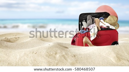 red suitcase in yellow sand and sea background  #580468507