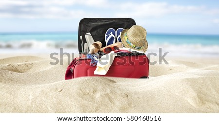 red suitcase in yellow sand and sea background  #580468516