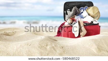 red suitcase in yellow sand and sea background  #580468522