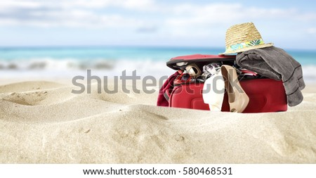 red suitcase in yellow sand and sea background  #580468531