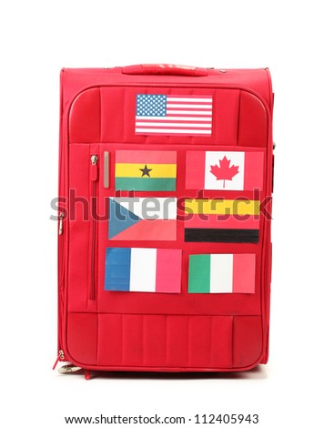 red suitcase with many stickers with flags of different countries isolated on white