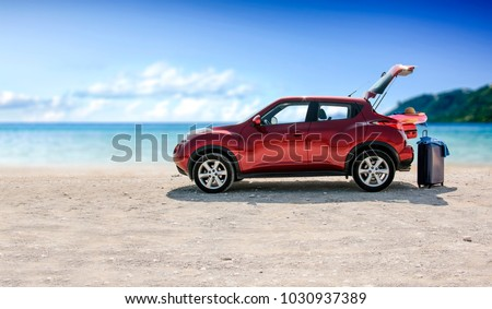 red summer car on beach with...
