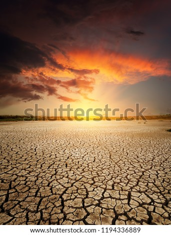 red sunset in dramatic clouds over drought earth