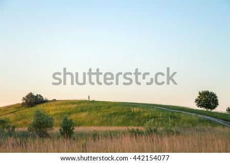 Stock Photo Red sunset over green hill with road. Road lane and cloudless sky. Nature design. Rural landscape in countryside. Rolling hill, trees, bushes, green field on warm sunset. Path turns uphill to the sky.