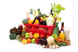Red supermarket shopping basket full of  fresh organic colorful foods and groceries with assorted ingredients on white background