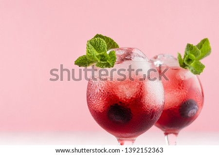 Red sweet cold party drinks in two elegant wineglasses with ice cubes, blueberry, green mint on pastel soft pink color background, closeup, top. #1392152363