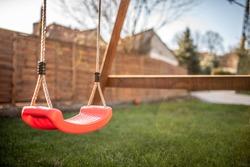 red swing in green garden