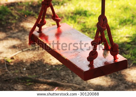Red swing under a shade tree