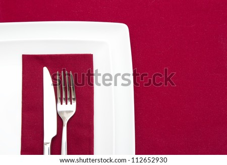 Red tablecloth with white plates and red napkin