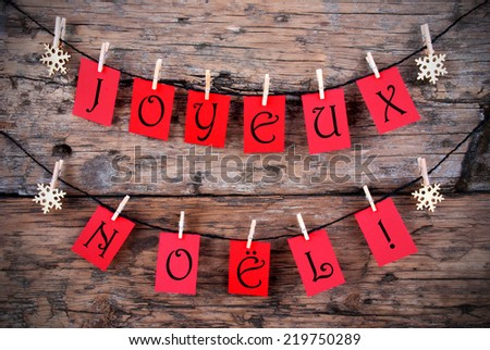 Red Tags Hanging on a Line with the French Words Joyeux Noel on it which means Merry Christmas