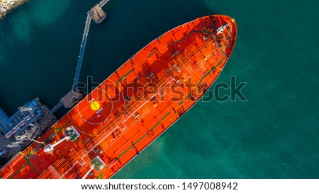 Red tanker ship loading and unloading oil and gas storage at industrial port, Business import export petrochemical oil and gas by tanker ship transportation, Loading arm oil and gas offshore platforms