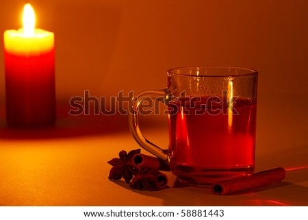 red tea in a glass, cinnamon sticks and star anise at candle light