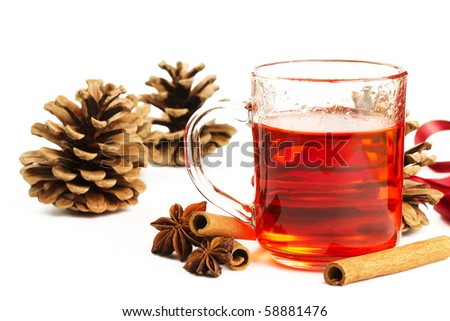 red tea in a glass, cinnamon sticks, star anise and some conifer cones on white background