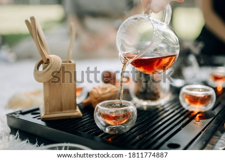 Red tea in a glass teapot is poured into cups. Tea ceremony in the park in the morning. The atmosphere of the tea ceremony.